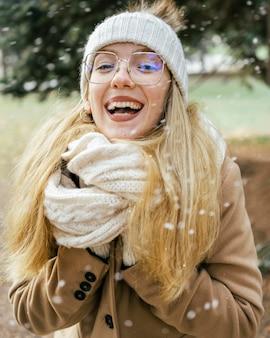 Vrouw met sjaal genieten van de sneeuwval in het park in de winter