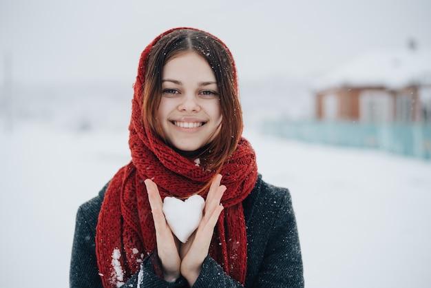 Vrouw met sjaal met een hart gemaakt van sneeuw