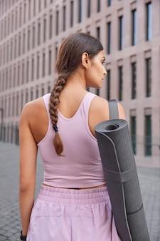 Vrouw met slank lichaam gekleed in sportkleding heeft gekamde vlecht draagt opgerolde karemat gaat yoga oefenen wandelingen in het centrum buiten