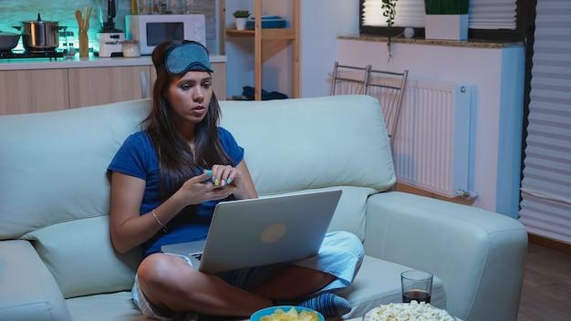 Vrouw met slapeloosheid die 's avonds laat met moeder op webcam praat. uitgeputte persoon in pijamas met slaapmasker met videogesprek op laptopcomputer die met ouders spreekt die internettechnologie gebruiken.