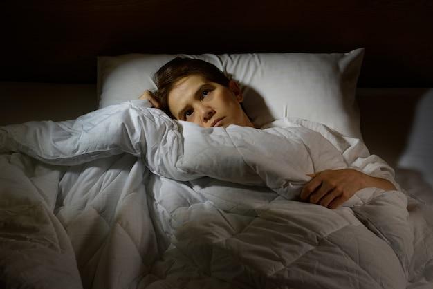Vrouw met slapeloosheid liggend in bed met open ogen