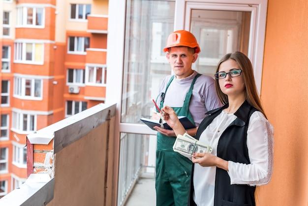 Vrouw met sleutels en dollars en opdracht gevend tot renovatie in appartement