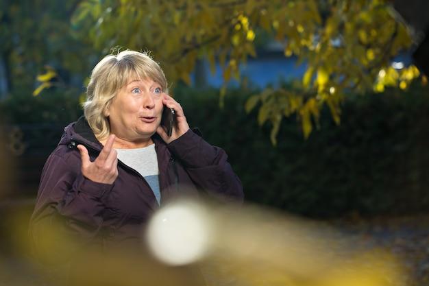 Vrouw met slimme telefoon buiten in de herfst