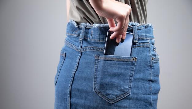 Vrouw met slimme telefoon in jeans pocket