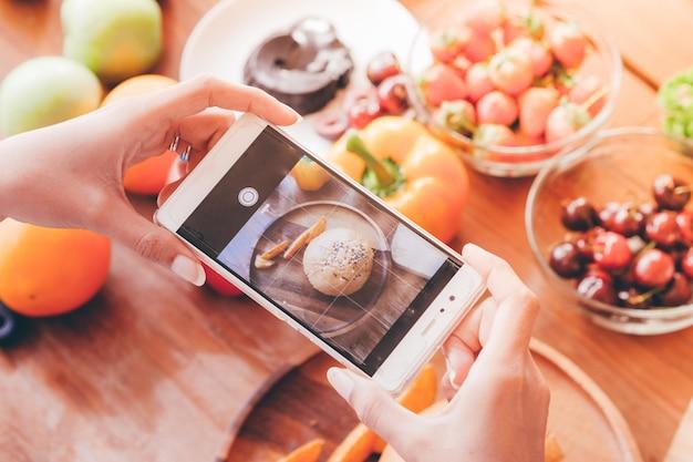 Vrouw met slimme telefoon neemt een foto van voedsel op tafel.