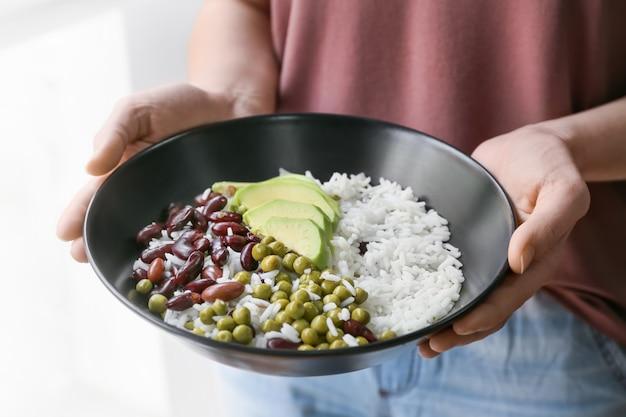 Vrouw met smakelijke rijst, bonen en avocado in kom, close-up