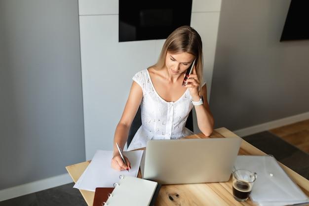 Vrouw met smartphone die op laptop thuiskantoor werkt