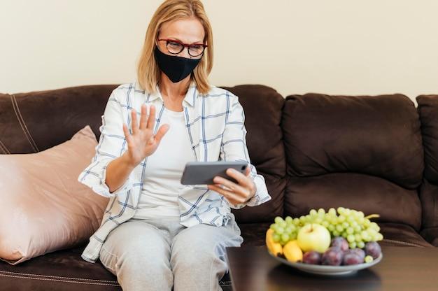 Vrouw met smartphone en katoenen masker thuis tijdens quarantaine