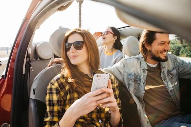 Vrouw met smartphone en positieve man in auto dichtbij dame die uit auto leunt
