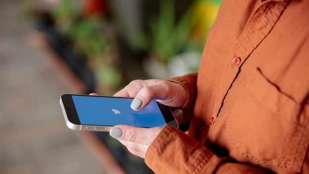 Vrouw met smartphone met het twitter-logo op het scherm thuis