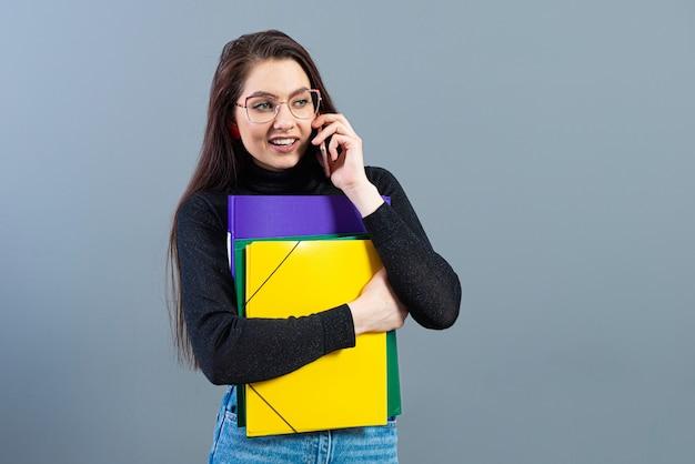 Vrouw met smartphone met kleurrijke mappen met documenten