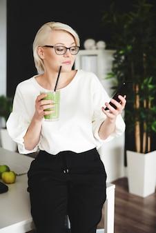 Vrouw met smoothie sms't op het werk