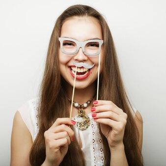 Vrouw met snor en bril op een stok