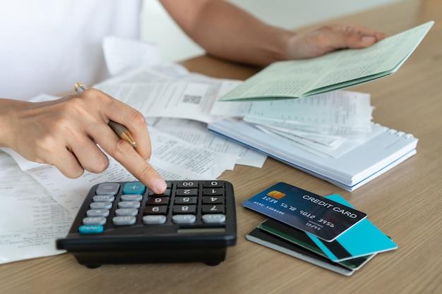 Vrouw met spaarrekening bankboekje en het gebruik van calculator, account en opslaan concept.