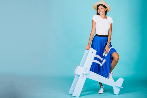 Vrouw met speelgoedvliegtuig op blauwe achtergrond