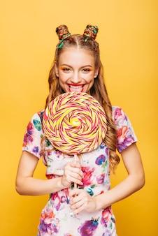 Vrouw met speelse blik die snoep eet