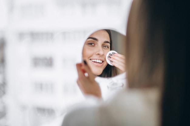 Vrouw met spiegel die make-up met stootkussen verwijdert
