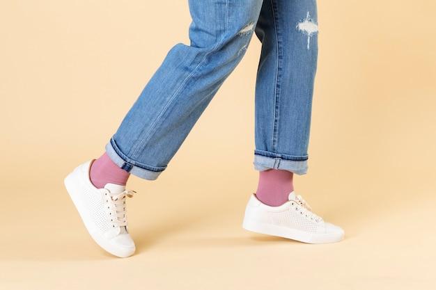 Vrouw met spijkerbroek en witte sneakers