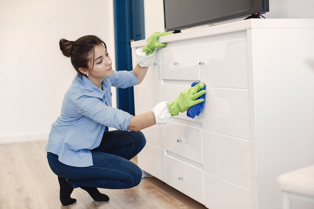 Vrouw met spons en rubberen handschoenen huis schoonmaken