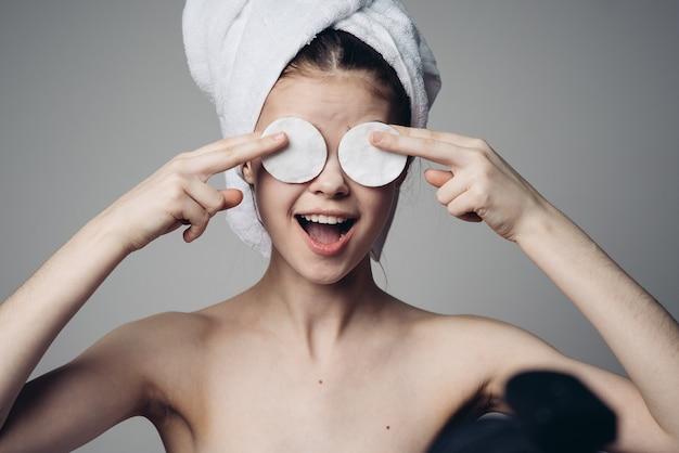 Vrouw met sponzen voor het reinigen van gezicht en hals