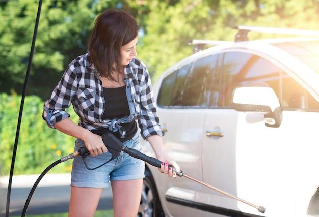 Vrouw met sproeier op self-car wash
