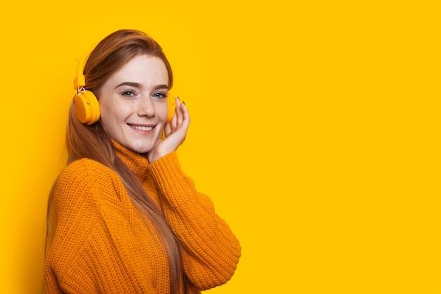 Vrouw met sproeten met rood haar lacht naar de camera in de buurt van gele vrije ruimte terwijl ze naar muziek luistert