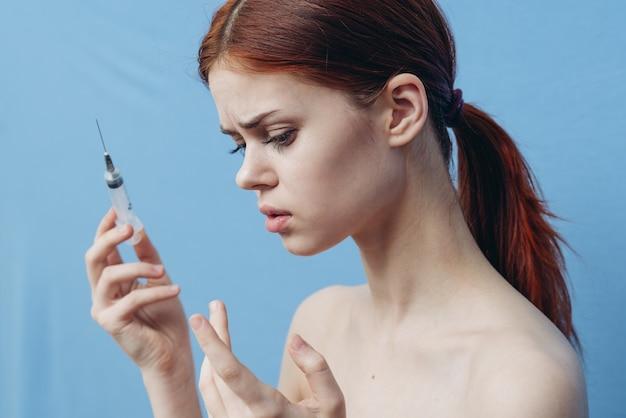 Vrouw met spuit in de buurt van gezicht botox verjonging injectie blauwe achtergrond