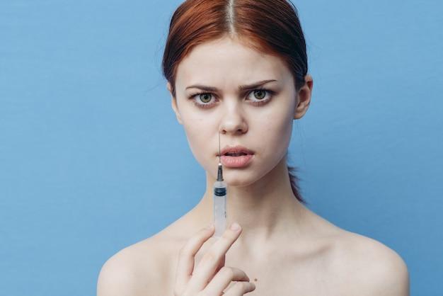 Vrouw met spuiten in de hand die injectie in de botox van de gezichtsverjonging geeft
