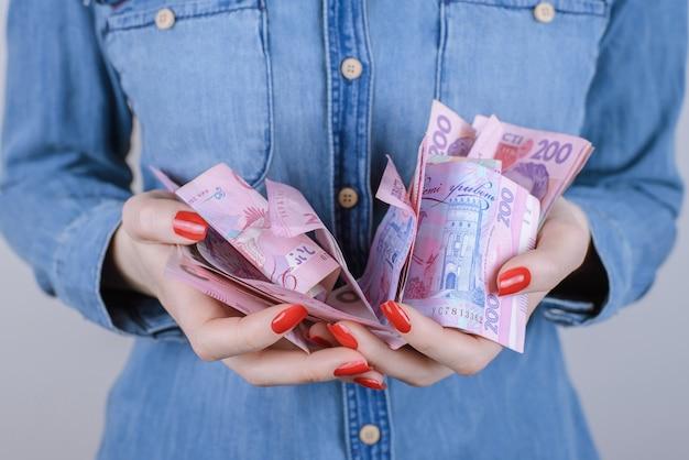 Vrouw met stapel van tweehonderd oekraïense hryvnia-bankbiljetten