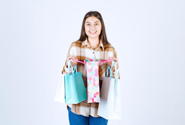Vrouw met stelletje boodschappentassen over witte muur.