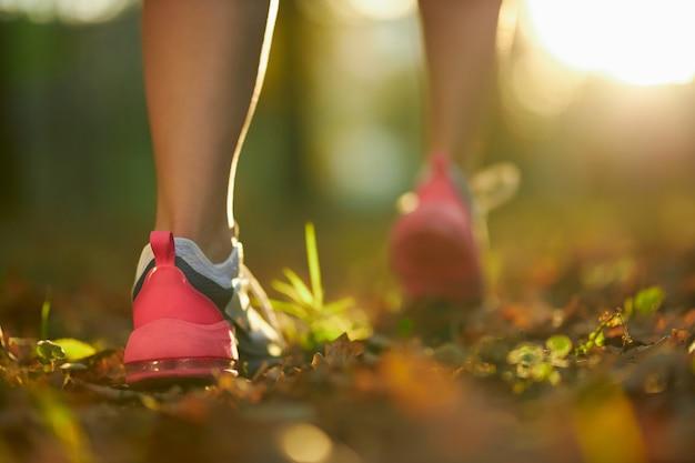 Vrouw met sterke benen die bij park in sportschoenen lopen