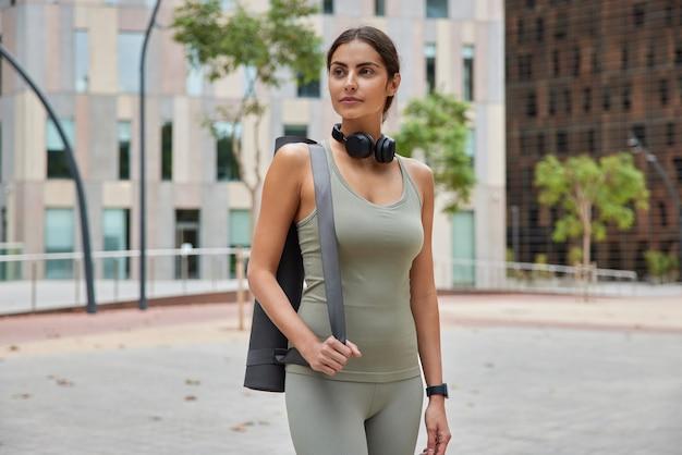 Vrouw met sterke weerstand gaat sporten bouwt regelmatig kracht van botten op heeft dagelijks yoga in de frisse lucht draagt sportkleding poseert met karemat buiten stelt doelen.