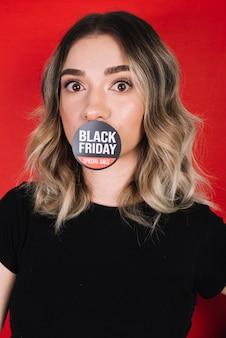 Vrouw met sticker op mond voor zwarte vrijdag