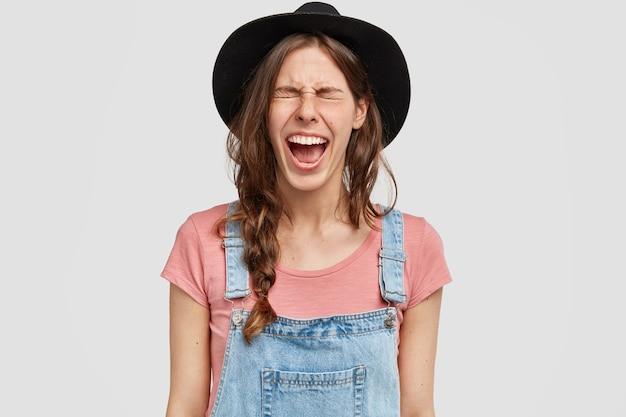 Vrouw met stijlvolle hoed en overall
