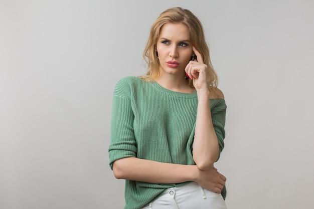 Vrouw met stijlvolle make-up en groene trui poseren op roze