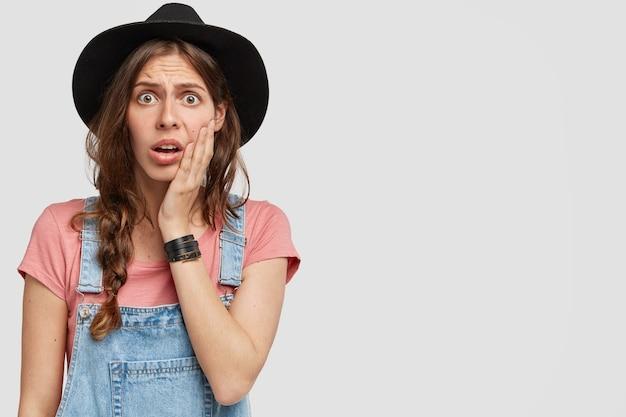 Vrouw met stijlvolle zwarte hoed en overall