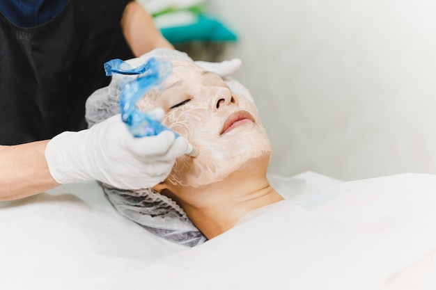 Vrouw met stimulerende gezichtsbehandeling bij professionele kliniek.