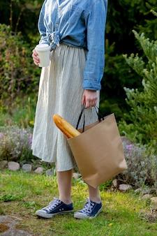 Vrouw met stokbrood in boodschappentas en kopje koffie in een tuin