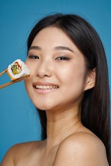 Vrouw met stokjes sushi rolt ontbloot schouders aziatisch uiterlijk zeevruchten dieet