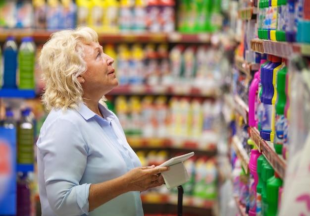 Vrouw met stootkussen die voor huishoudelijke detergentia winkelen