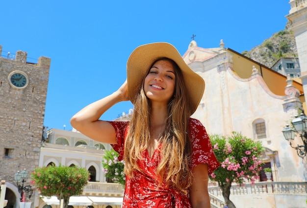Vrouw met strohoed en rode kleding met dorp taormina, sicilië, italië