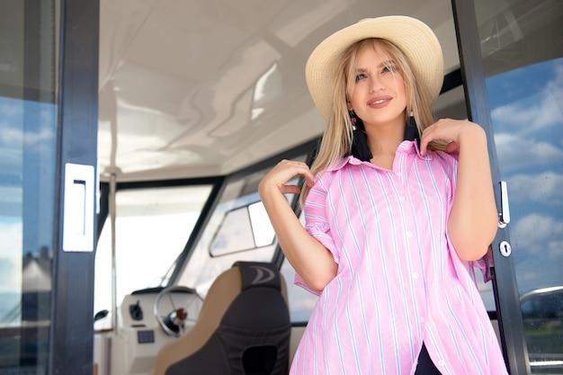 Vrouw met strohoed rust in de zomer uit op een jacht