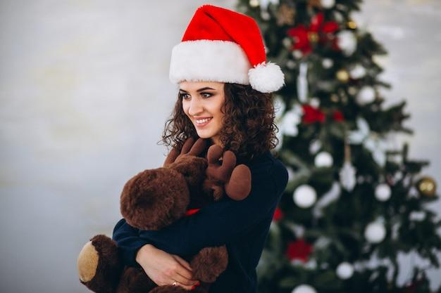 Vrouw met stuk speelgoed amerikaanse elanden door kerstmisboom
