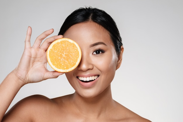 Vrouw met stukjes sinaasappel in de buurt van haar gezicht