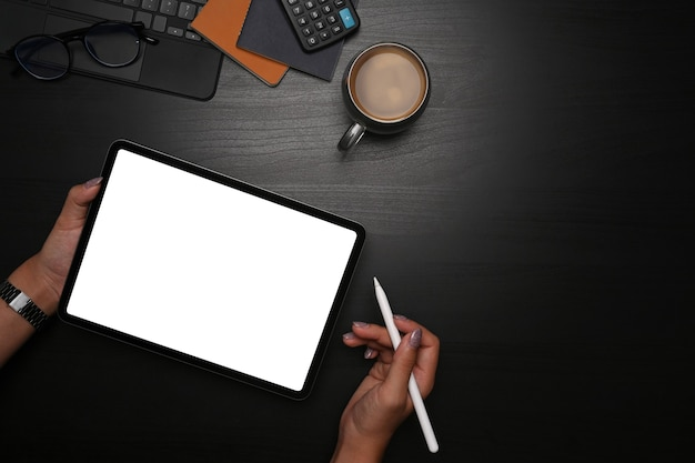 Vrouw met stylus pen en digitale tablet met leeg scherm op zwarte tafel.