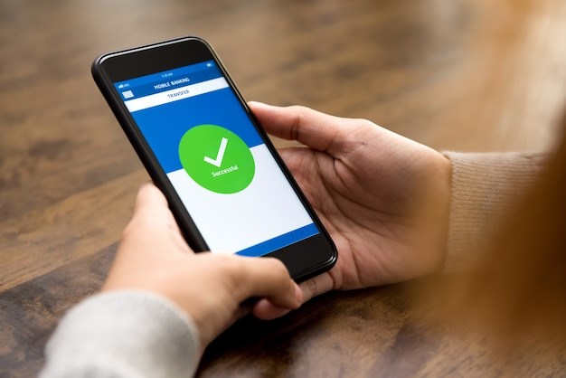 Vrouw met succes geld online overgedragen via elektronische internetbankieren-applicatie op smartphone