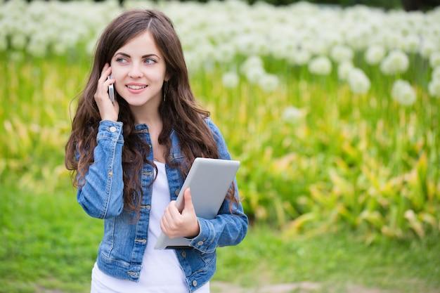 Vrouw met tablet-computer en praten over de telefoon