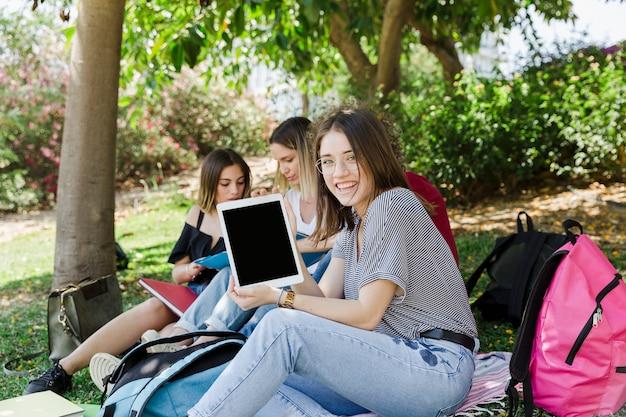 Vrouw met tablet met vrienden in park