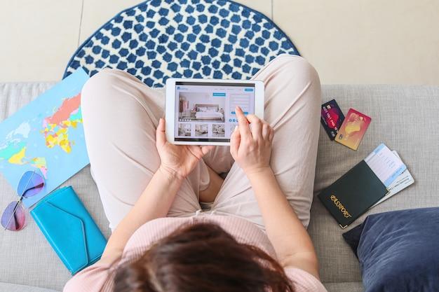 Vrouw met tabletcomputer boeken kamer in hotel thuis