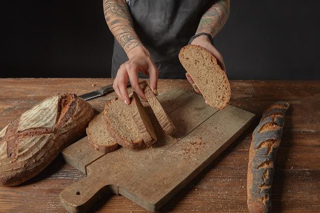 Vrouw met tatoeages op haar handen graanbrood snijden op een houten plank